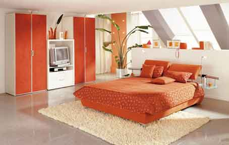 Comfortable-bedroom-with-inclined-windows-and-massive-warm-colored-bed-and-ceiling-high-wardrobe