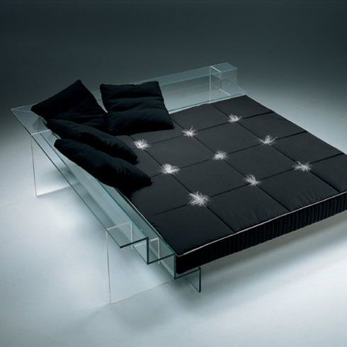 Stunning-glass-bed-with-four-black-pillows-and-mattress-decorated-with-fluff