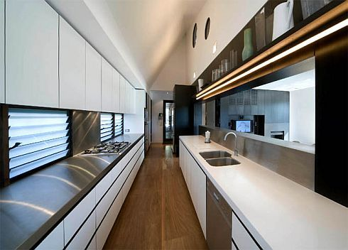 Luxury-long-kitchen-area-with-many-cupboards-granite-countertop-sink-stove-cabinets-and-wooden-floor