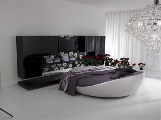 Luxury-round-bedroom-furniture-in-grey-with-black-cabinet-and-modern-chandelier