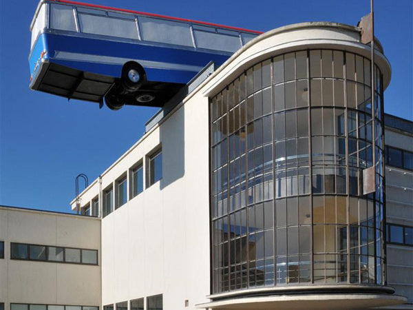 Strangely Unexpected: Full-sized Coach Balancing on the Edge of De La Warr Pavilion