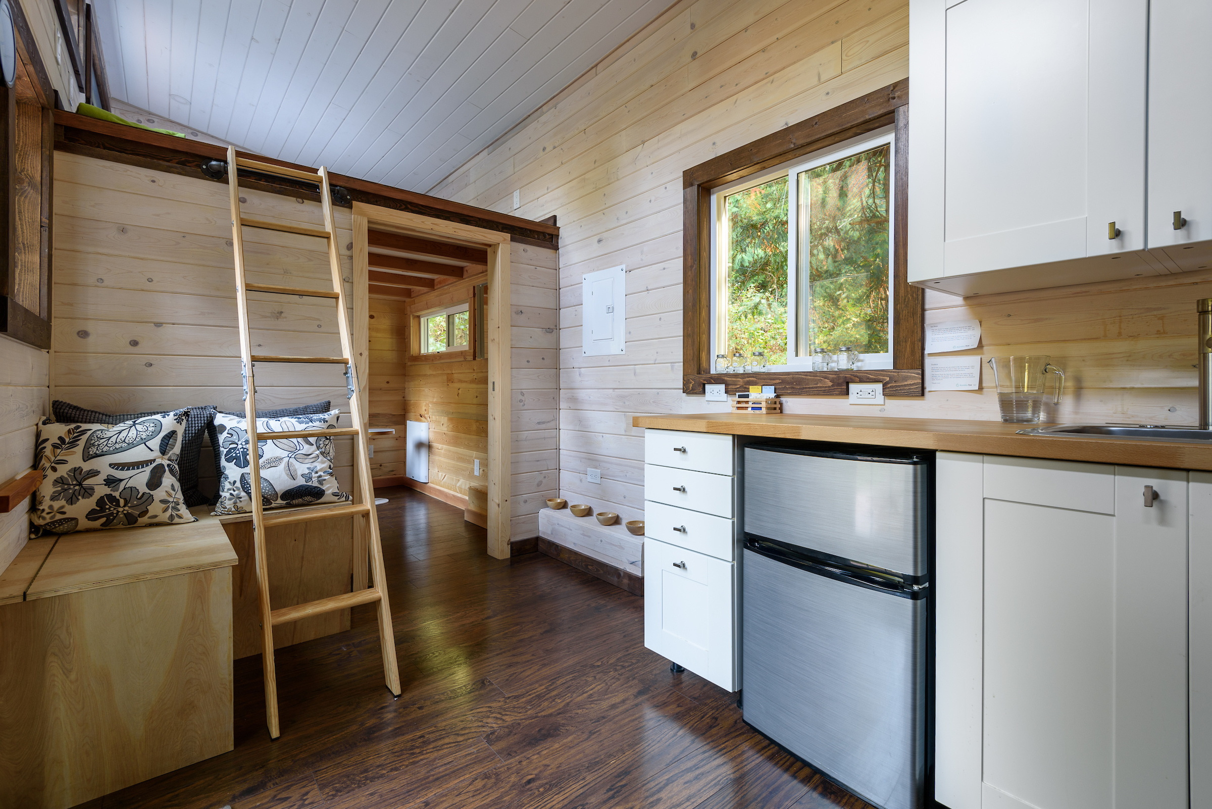 Interior design of a dining room and kitchen in a tiny rustic log cabin.