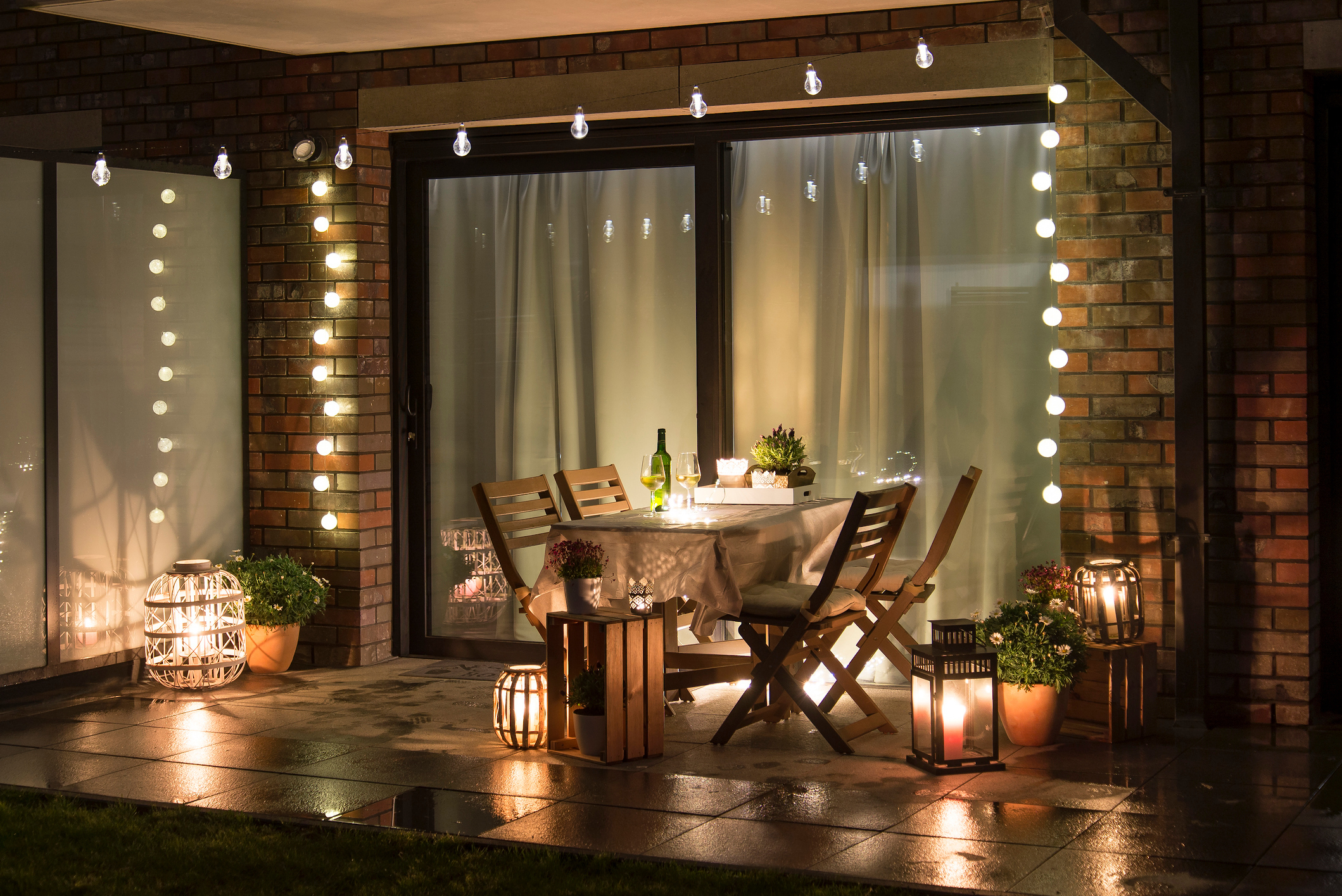 Summer evening terrace with candles, wine and lights, wet pavements