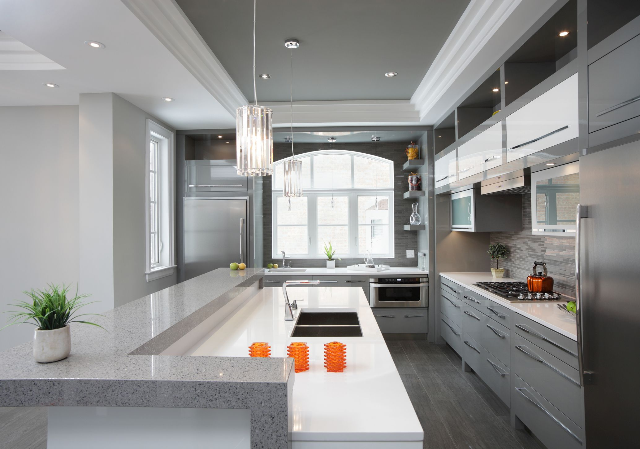 Shades of gray in the cabinets, backsplash, countertops, ceiling, and floors.