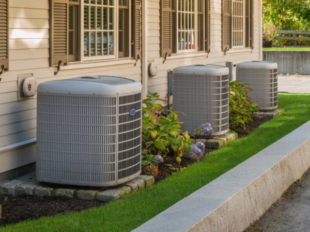 Row of HVAC units outside of homes