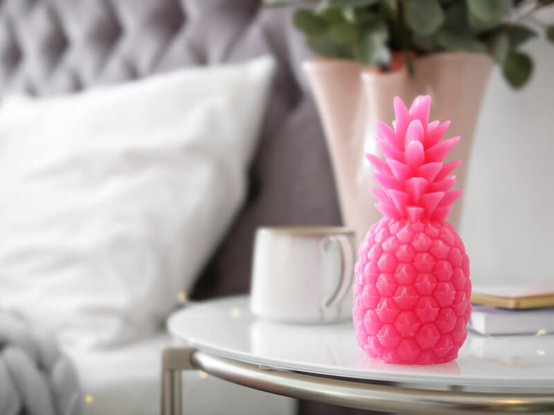 Pink pineapple candle on bedside table