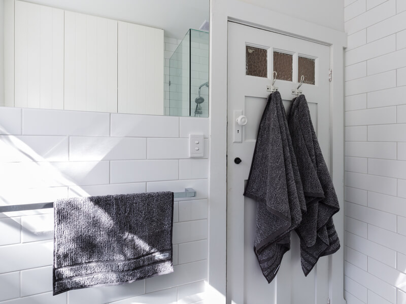 White bathroom with towels on the door