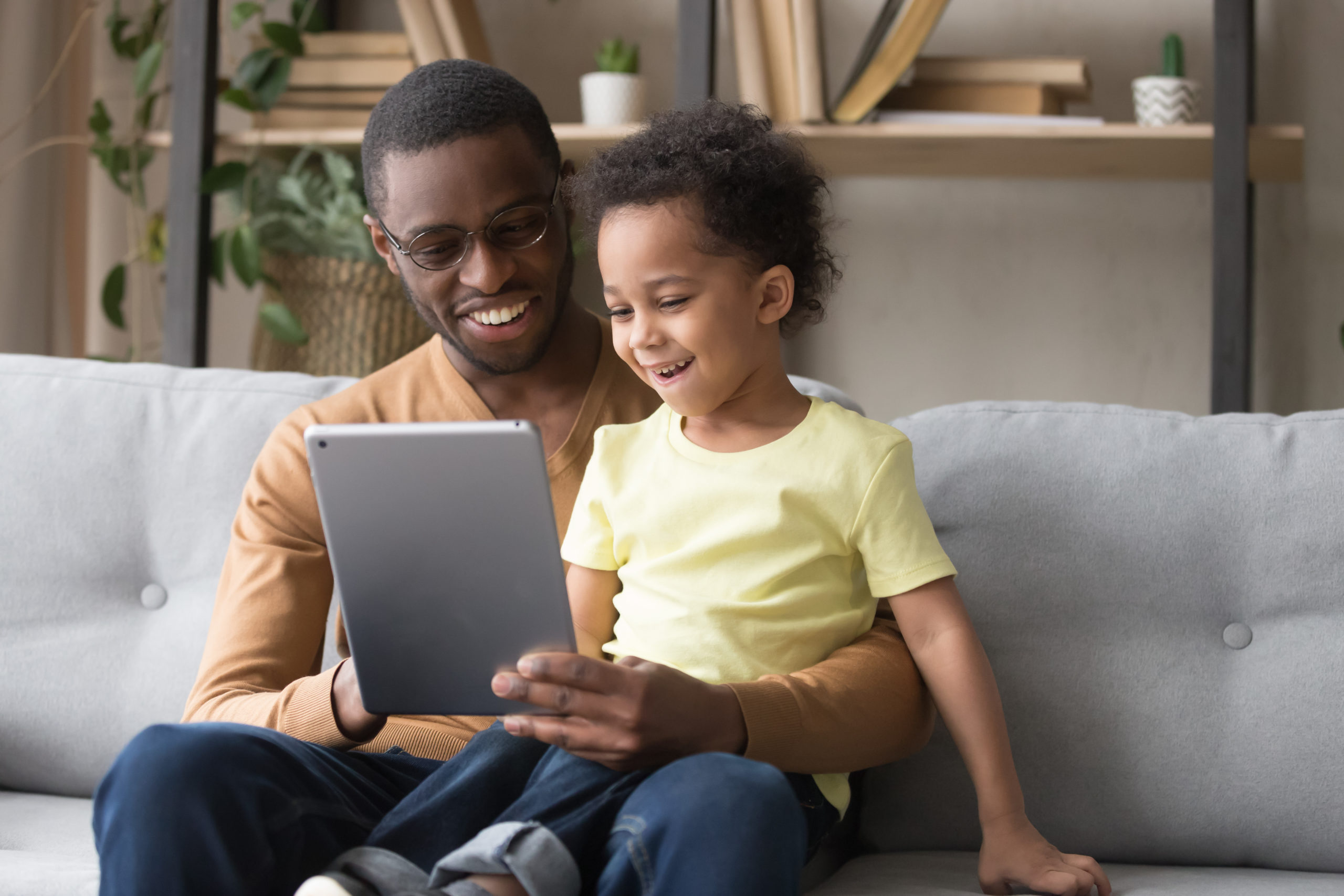 father and daughter sitting together on couch laughing at tablet screen